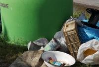 Kierowca bordowego Opla Corsa podrzuca śmieci w Piekarach